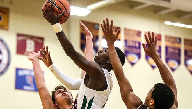 Crispus Attucks Tigers guard Harold Bennett (0) goes up for a shot between Brebeuf defenders, during second half action of the 3A boys Sectional 27 game between Brebeuf and Crispus Attucks, at Guerin Catholic High School in Noblesville, Ind., Wednesday, Feb. 28, 2018. Crispus Attucks won, 58-53.