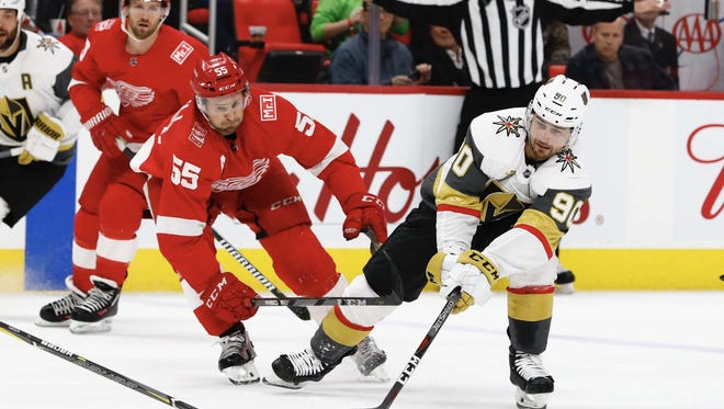 Detroit Red Wings defenseman Niklas Kronwall (55) and Vegas Golden Knights left wing Tomas Tatar (90) battle for the puck in the first period at Little Caesars Arena on Thursday, March, 8, 2018.