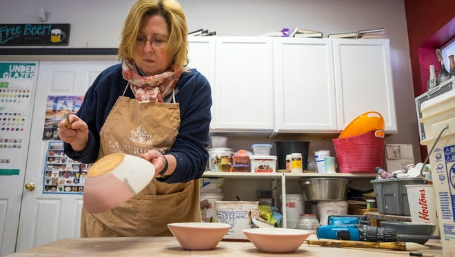 Deborah Bassett-Maxwell uses a brush to spatter glaze on clay bowls inside her studio, Red Mudd Studio, in Kimball March 9. Bassett-Maxwell has donated bowls to the Empty Bowls fundraiser each of its 15 years.