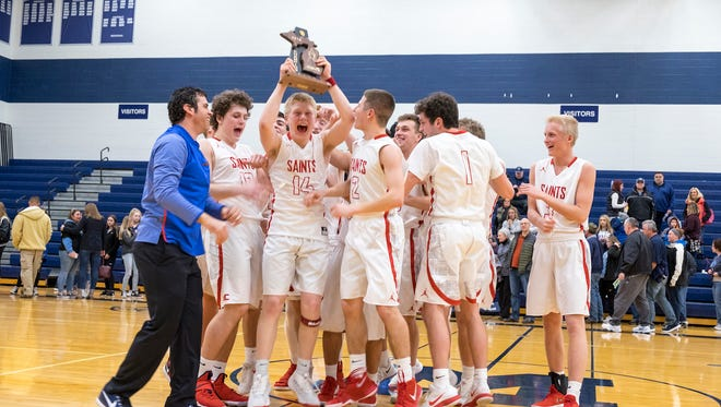 The St. Clair High School Saints celebrate defeating Richmond High School 65-50 during the MHSAA Class B District Finals at Marysville High School March 9.