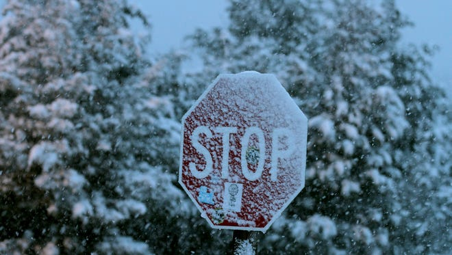 Snow clings to a stop sign in the Monmouth Service area along the Garden State Parkway in Wall Township Tuesday morning, March 13, 2018.