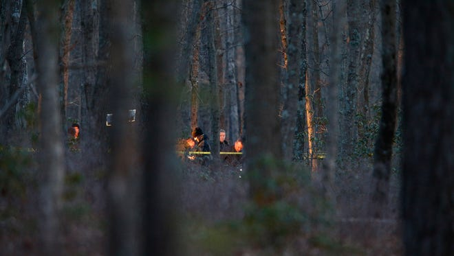 Investigators are shown in Colliers Mills Wildlife Management Area, south of South Stump Tavern Road in Jackson Township Monday evening.