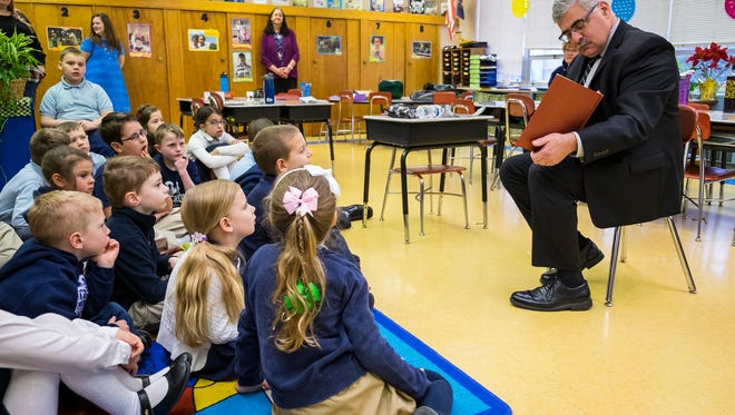 St. Clair County Probate Judge John Tomlinson reads to students at Holy Cross Catholic School Wednesday, March 21. Tomlinson read to the class after receiving a letter written by one of the students.
