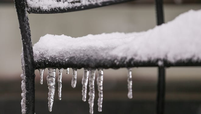 Snow and ice build up on patio furniture in downtown Indianapolis, Saturday, March 24, 2018.