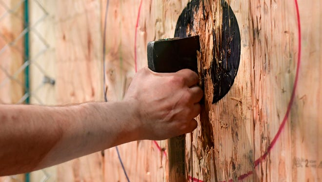 Ax Trainer Paul Martin pulls an ax out of the wall at Meduseld Meadery in Lancaster on March 28, 2018. The meadery just opened up an indoor ax-throwing range.