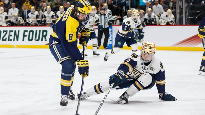 Notre Dame Fighting Irish Defenseman Matt Hellickson (5) defends Michigan Wolverines forward Jack Becker (8) in the first period in the 2018 Frozen Four college hockey national semifinals at Xcel Energy Center on April 5, 2018.