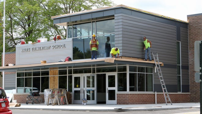 A construction crew works on the entrance of Wales Elementary Schoolin this file photo. The district is considering options such as moving the music classroom to accommodate additional students.