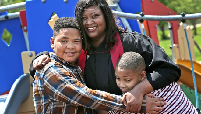 Porshea Johnson gets a hug from her sons, Jovan, left, and Jamal Johnson, in the Kennedy-King neighborhood park, Friday, May 11, 2018. A former resident of Dayspring Center when she was homeless in 2012, and a recipient of a Nina Mason Pulliam Scholarship award, Johnson is graduating from IUPUI with a degree in general studies with an emphasis in philanthropy.  This weekend she will also celebrate Mother's Day on her birthday, May 13.