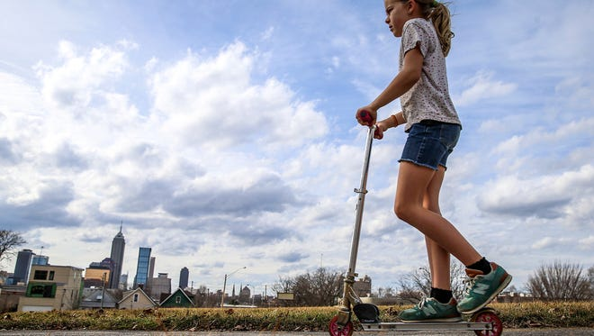 The Indianapolis skyline is seen at left, as Natalie Tolbert, 9, takes advantage of unseasonably warm weather and rides her scooter through Highland Park in Indianapolis, Tuesday, Feb. 20, 2018.