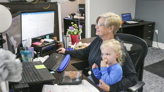 Jr. Processor Robin Mullikin holds her granddaughter Kaylynn Cogan while working in the Bailey & Wood Financial Group offices in Whiteland, Ind. on Thursday, April 26, 2018.