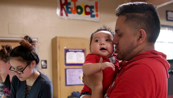 Felipe Vargas-Perez, 25, of Salem, holds his 3-month-old daughter, Jaylanie Vargas-Rosas, as dinner is served inside an emergency family shelter at Queen of Peace Catholic Church in Salem on Monday, May 14, 2018.