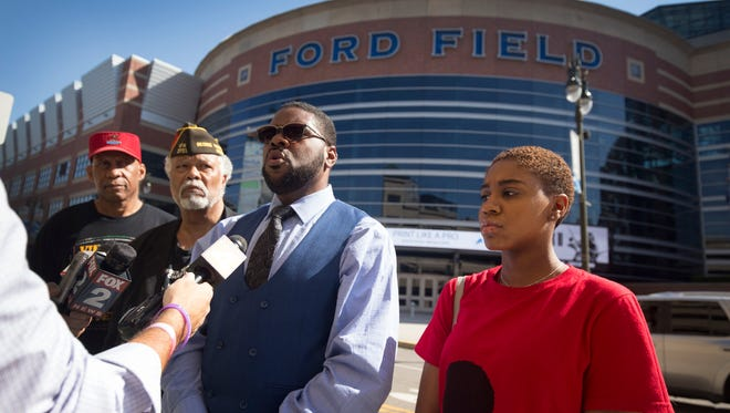 From left, Tyron Allen, activist Sam Riddle, Rev. Charles Williams and Kayla Kennard, the Wayne State University National Action Network student chapter president, stand in front of Ford Field on Friday, May 25, 2018. Williams, the president of the National Action Network Michigan chapter, made a statement regarding the recent controversial NFL policy penalizing athletes who chose to kneel during the national anthem.
