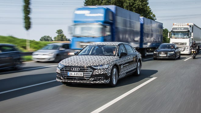 An Audi A8 in testing mode works on refining a suite of semi-autonomous driver-assist features that allow drivers to hand over some tasks to the automobile, though they must check in with the steering wheel often to keep the system active.