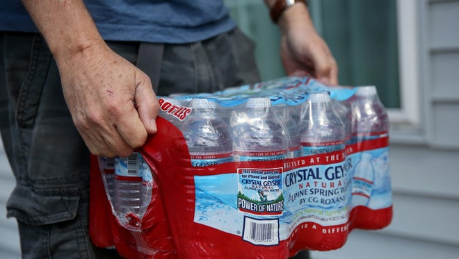 Bob Cook, of Keizer, carries a case of water being given out during a Meals on Wheels delivery route in Salem on Friday, June 1, 2018.