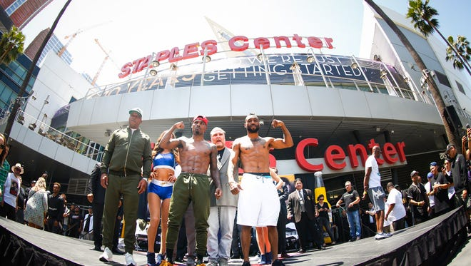 Austin Trout, right, and Jermell Charlo pose for photographers after Friday weigh-in.