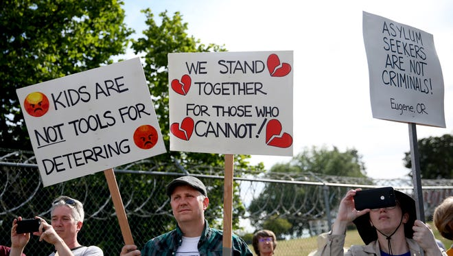 Doug O'Loughlin, of Portland, from left, Steve Lehman, and Torey Lehman, both of Eugene, attend a rally to protest the detaining of asylum seekers at the Federal Correctional Institution in Sheridan on Monday, June 18, 2018.