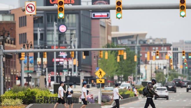 People are seen crossing Woodward Avenue near Columbia Street in downtown Detroit, Saturday, June 9, 2018.
