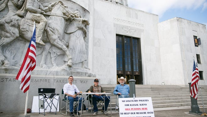 (Left to right) Richard LaMountain, Jim Ludwick and David Olen Cross with Oregonians for Immigration Reform collect the final signatures to get their Initiative Petition 22 on Friday, July 6, 2018. The group said they have at least 20,000 signatures over the 88,184 required to get the item on the November ballot.