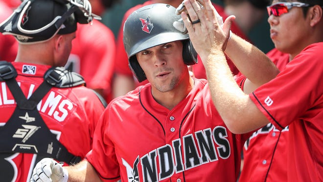 Indianapolis Indians infielder Adam Frazier (26) is congratulated in the dugout after he scored on a single hit by Indians catcher Ryan Lavarnway (23), leaving the score 5-2 in the bottom of the fifth inning of their game against the Columbus Clippers at Victory Field in Indianapolis, Sunday, July 8, 2018. The Indians won, 5-4.