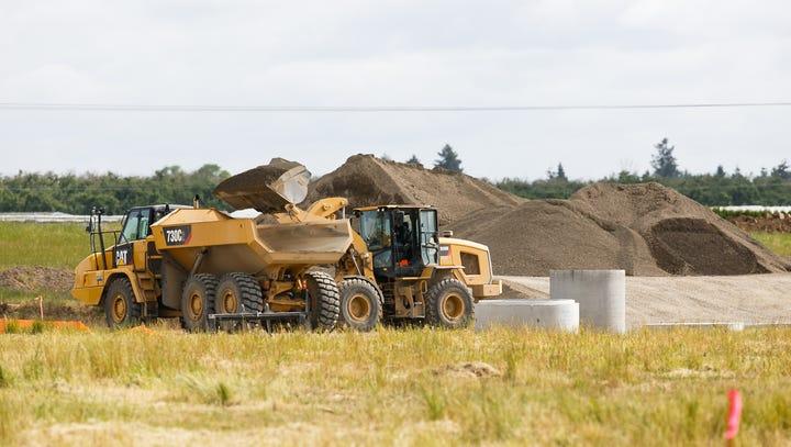 Work crews excavate dirt at a pesticide-contaminated