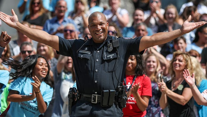 """Officer Ethan Forrest from Indianapolis Metropolitan Police Department dances and sings along while filming a final clip for IMPD's lip-sync battle video to Justin Timberlake's """"Can't Stop the Feeling!"""" on Monument Circle in downtown Indianapolis, Thursday, July 12, 2018."""