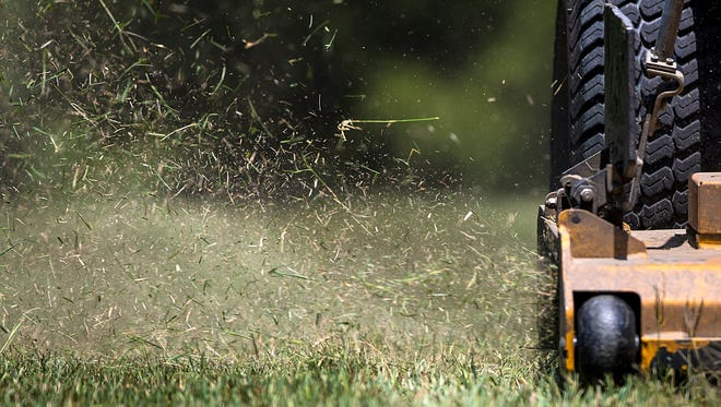 Grass flies as Larry Webb mows a lawn in Greenwood, Ind., Friday, July 13, 2018. GreenPal is a Nashville-based smartphone application that recently launched in Indianapolis, allowing users to make appointments with local, vetted lawn care professionals.