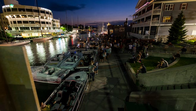 People party along the Black River on Boat Night Friday, July 13, 2018 during Boat Week in Port Huron.