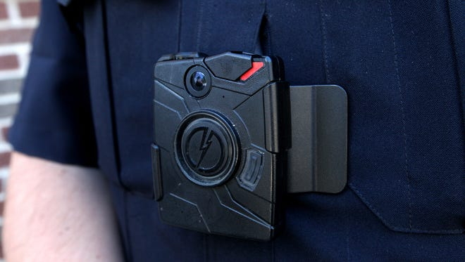 A black camera clipped to a police uniform.