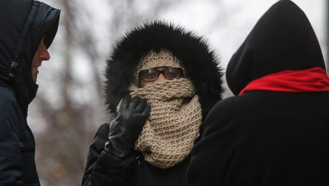 Valerie Coleman (center) of Detroit covers her face while waiting for a bus on Woodward near Congress in downtown Detroit on Tuesday November 18, 2014, as cold weather and snow moves into the area.