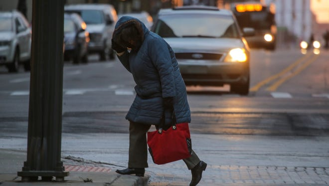 A woman shields herself from the cold wind while crossing the street at W. Fort St. and Griswold in downtown Detroit on Tuesday November 18, 2014 as cold weather and snow moves into the area.