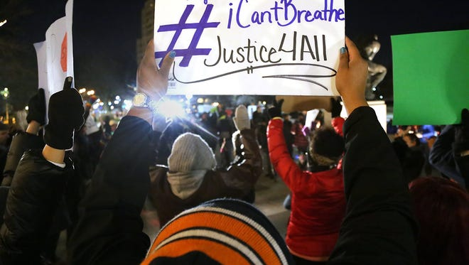 Protestors gather in front of the Detroit Institute of Arts museum in Detroit to march for justice for Eric Garner and Michael Brown who where both killed by police officers during Noel Night on Saturday , Dec. 6, 2014.