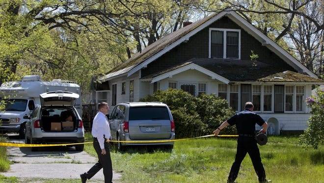 Law enforcement officials cordon off a home as they execute a search warrant, Wednesday, May 18, 2016, in Norton Shores.