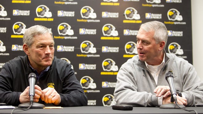 Iowa football coach Kirk Ferentz, left, is joined by athletic director Gary Barta during a press conference held to announce Iowa's 2014 Outback Bowl bid on Dec. 8, 2013.