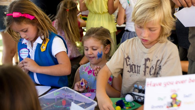 Ally Gray, 4, (middle) smiles as she makes progress on her art work during the 3rd annual McCallum Theatre Family Fun Day, Sunday afternoon, October 19, 2014.