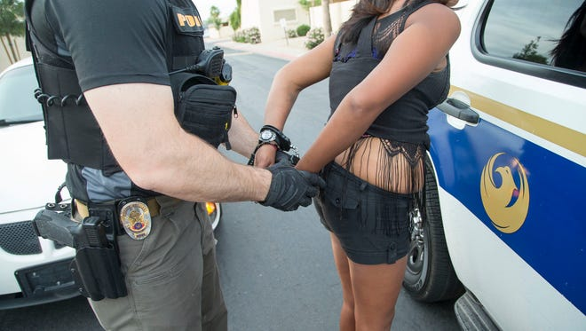 Phoenix Police detectives from the Vice Enforcement Unit arrest a prostitute who was a heroin user in west Phoenix on Friday, May 16, 2014. This was a joint operation with Project Rose, a Phoenix collaboration that aims to divert prostitutes into social programs. This program was to raise public awareness about prostitution and human trafficking, and to provide support, information and education to these women.