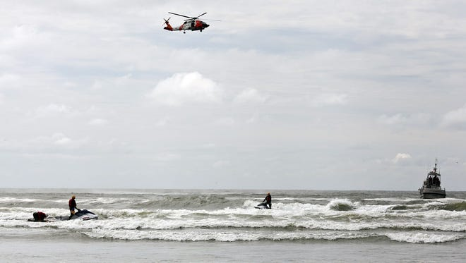 Coast Guard helicopter and motor life boat help surf rescue swimmers from the South Pacific County Technical Rescue team