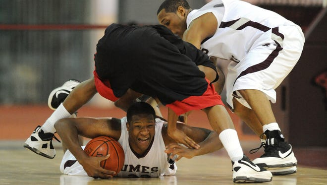 UMES's #33 Chris Conner takes control of a loose ball from Winston-Salem State University's #2 Jemarcus McClinton during Saturday's game in Princess Anne.