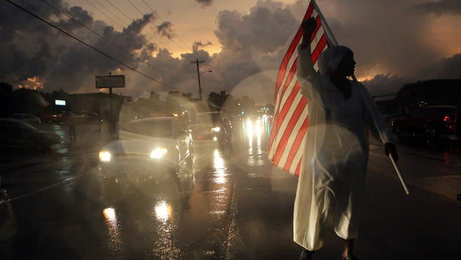 Gina Gowey, of Ferguson, Mo., protests on West Florissant Ave., Sunday, Aug. 9, 2015, in Ferguson, on the one-year anniversary of Michael Brown being shot and killed by Ferguson Police Officer Darren Wilson. (Huy Mach/St. Louis Post-Dispatch via AP)  EDWARDSVILLE INTELLIGENCER OUT; THE ALTON TELEGRAPH OUT; MANDATORY CREDIT