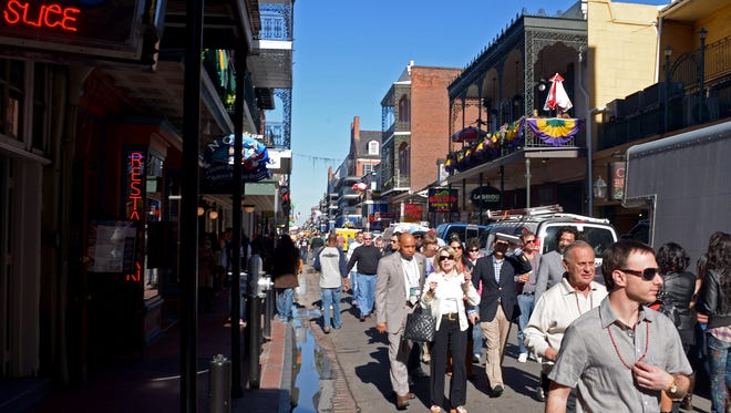 Tourists walk down Bourbon Street in the French Quarter.