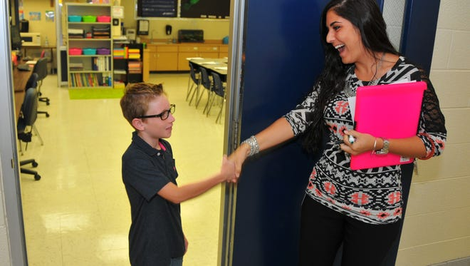 """Wednesday was the first day of school for Brevard County students, and Saturn Elementary School in Cocoa was kicking off the school year with a super hero theme, """"learning gives us super powers."""" Garret Cox is greeted by his 3rd grade teacher Shannon Albright."""