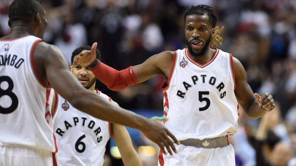 Toronto Raptors' DeMarre Carroll celebrates a 3-point basket against the Miami Heat with teammate Bismack Biyombo during the second half of Game 7 of the NBA basketball Eastern Conference semifinals in Toronto, Sunday, May 15, 2016. (Frank Gunn/The Canadian Press via AP) MANDATORY CREDIT