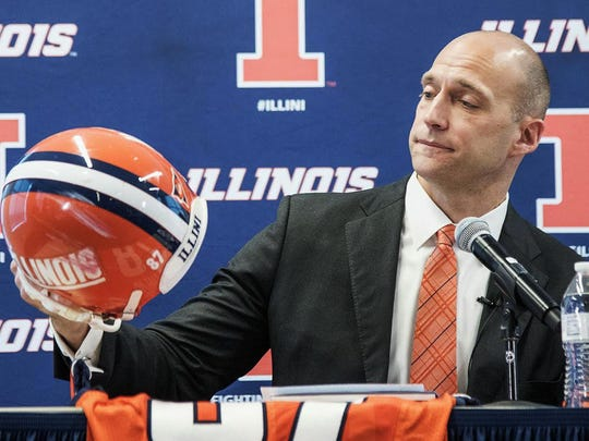 Josh Whitman, holds up his old football helmet as he is announced as the new the new Illinois athletic director during a news conference at Bielfeldt Athletic Administration Building in Champaign, Ill., Thursday, Feb. 18, 2016. The 37-year-old former Illinois and NFL player was most recently the athletic director at Washington University in St. Louis. (Heather Coit/The News-Gazette via AP) MANDATORY CREDIT