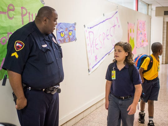 Lafayette Police Department Corporal Jarvis Mayfield watches a hallway during a class change at Paul Breaux Middle School in Lafayette, La., Friday, Nov. 20, 2015.