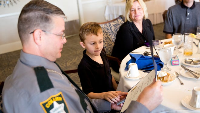 Trynt Thompson, 7, inspects the badge given to his father, Corporal Steven Thompson, for an act of heroism during the Naples Chapter of the Sons of the American Revolution at the Public Service Awards luncheon at The Club at Longshore Lake Thursday, Nov. 10, 2016 in Naples. The awards ceremony is a time to honor local police, firefighters, and EMS.