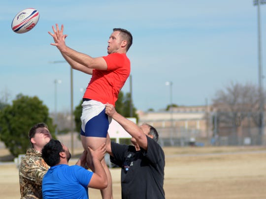 Members of the Horny Toad Rugby Football Club lift Travis Woodard, practicing  a drill called the line-out.  A line-out is awarded to a member of the opposing team if the ball is kicked into touch (out of the field of play) during a match.