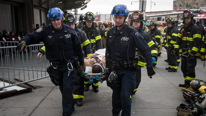 Authorities carry a person injured in a train derailment away from Atlantic Terminal in New York on Jan. 4, 2017.