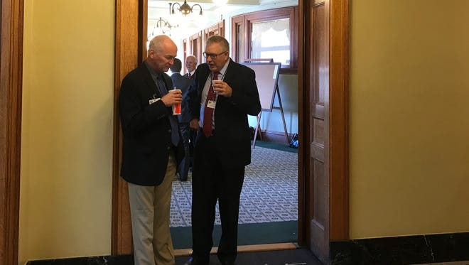 Lobbyists Kevin Kouba, left, and Steve Willard, right, talk Thursday afternoon outside a Senate hallway that has become a home base for lobbyists. Senators earlier in the day proposed barring lobbyists from entering their chamber and adjacent hallways during working hours.