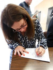Victoria Trujillo fills out a voter registration form after her naturalization ceremony at the Westchester County Courthouse in White Plains on Wednesday, Feb. 10, 2016.