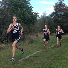Pinckney's Austin Wicker sprints toward the finish line, followed by teammates Ryan Talbott in second and Isaac Harris in third. Wicker finished first, Harris second and Talbott third, as they led the Pirates past Hartland in a dual cross country meet on Tuesday at Hudson Mills Metropark.