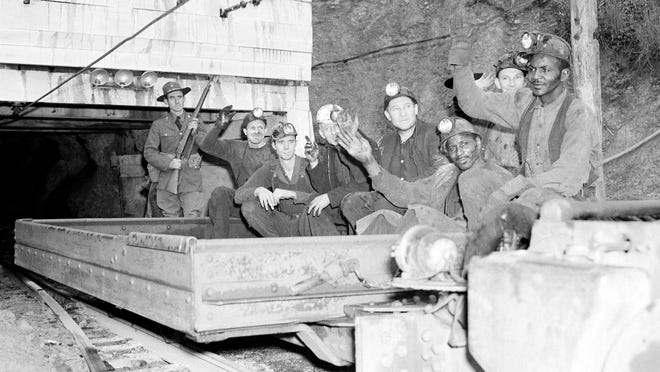 To the accompaniment of cat-calls shouted by pickets outside the workings, workers are shown entering  one of the coal mines near Harlan, Kentucky, on May 17, 1939.     National guardsmen escorted them through the picket lines.